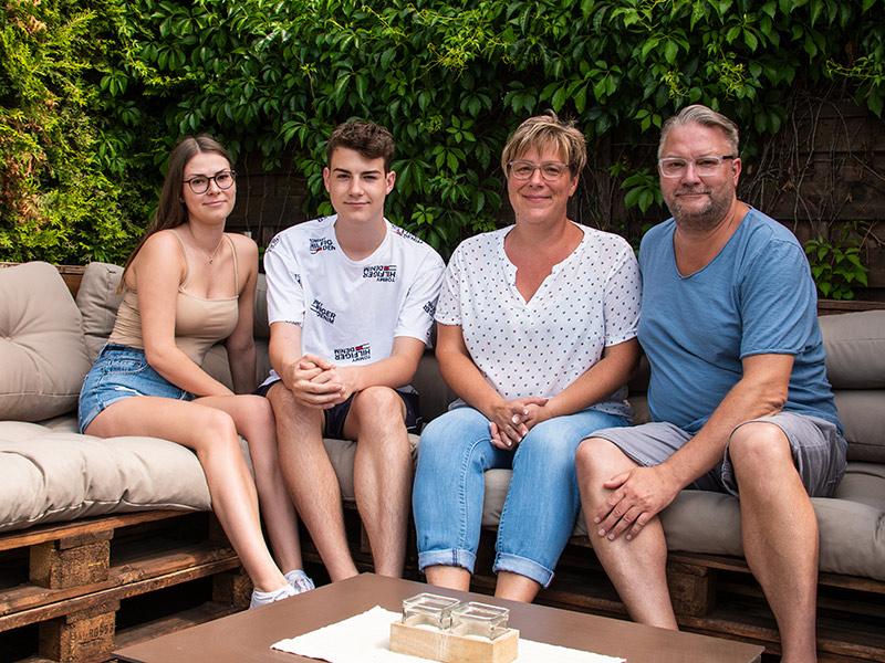 Joline Sill, Jerome Sill, Christiane Sill und Ronald Sill sitzen nebeneinander auf einer Couch auf der Terasse