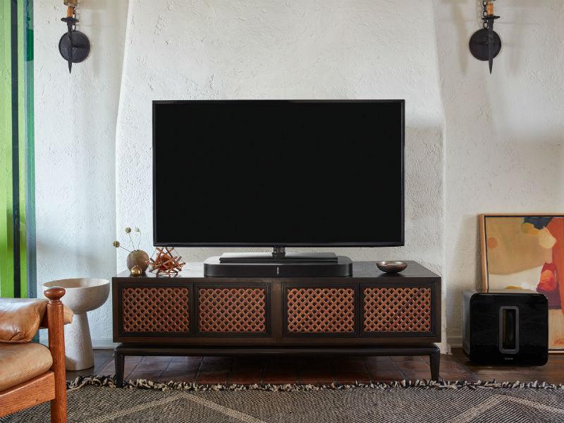 Fernseher steht auf SONOS Playbase auf einem Sideboard und daneben der Sonos SUB