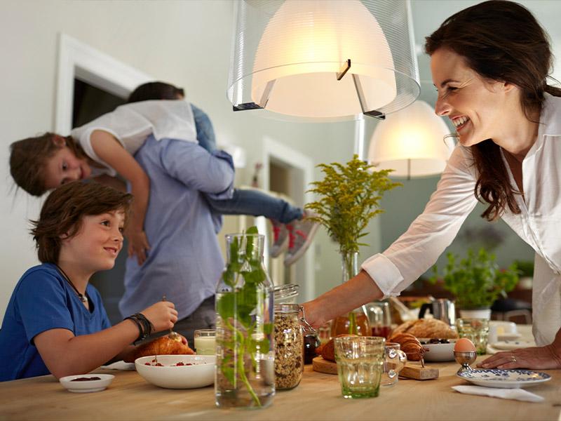 Familie sitzt am Frühstückstisch mit Philips Hue Lampen, steuerbar über den Google Assistant